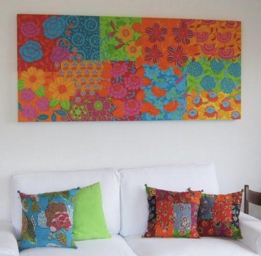 Mistura de estampas na decoração, sofá branco com almofadas coloridas e um quadro repleto de cor na parede em cima do sofá.