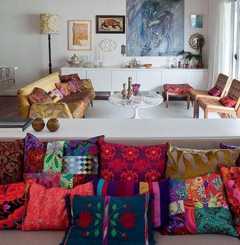 Misturas de estampas na decoração, sofá repleto de almofadas diferentes.