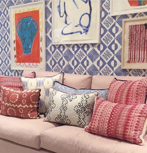 Mistura de estampas na decoração, parede com tecido azul e branco estampado, sofá rosa claro e almofadas nessas duas cores.