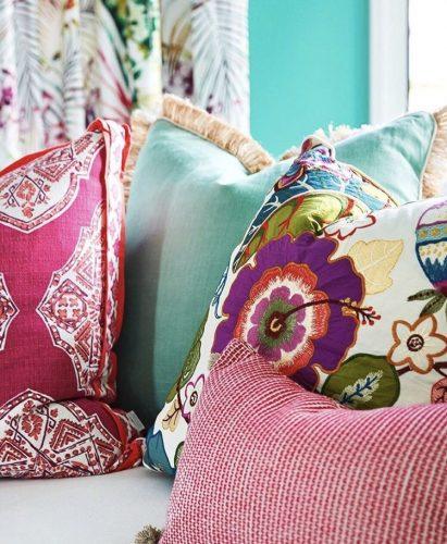 Mistura de estampas na decoração, almofadas estampadas com a cor vermelha em comum.