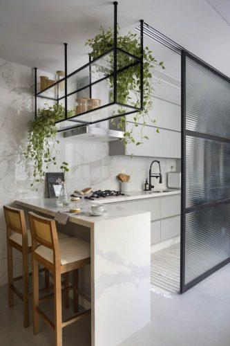 cozinha aberta com divisórias e armário suspenso com perfis preto no projeto de Beta Arquitetura