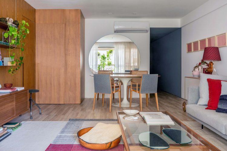 Sala com mesa redonda de jantar, espelho redondo ao fundo com cadeiras estofadas.