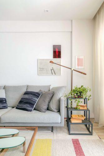 Sala com sofá cinza e abajur de pé aolado