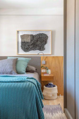 Quarto de casal com meia parede em madeira, cabeceira estofada e colcha azul