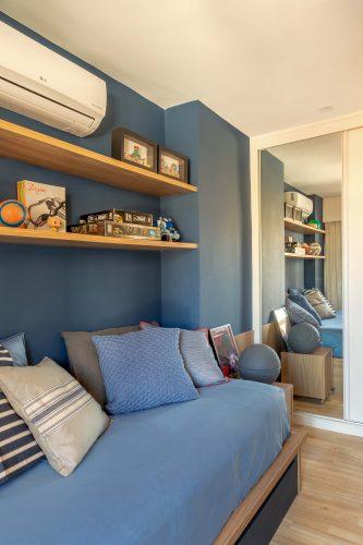 Quarto de menino com parede azul e cama com colcha da mesma cor