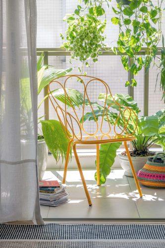 Na varanda uma cadeira de ferro amarela
