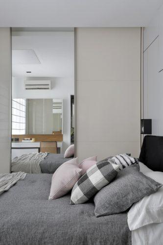 Apartamento de recém-casados no Jardim Botânico. Quarto de casal com porta e armário espelhado e roupa de cama cinza