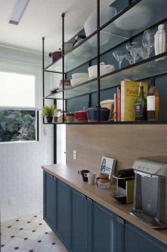 Apartamento de recém-casados no Jardim Botânico. Estenta superior vazada na cozinha abriga a louça e na parte de baixo armario azul com bancada em madeira.
