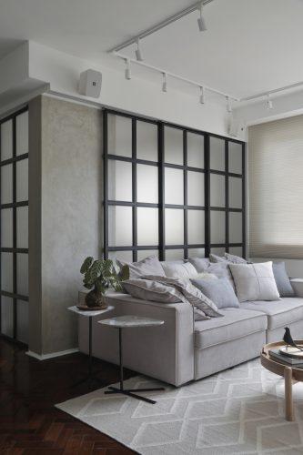 Apartamento de recém-casados no Jardim Botânico, esquadria preta separa a sala do escritório e um sofá grande cinza