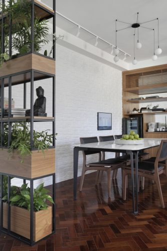 Apartamento de recém-casados no Jardim Botânico, floreira alta separa o hall de entrada da sala de jantar