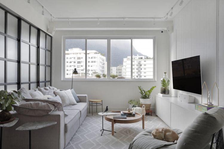 Apartamento recém casados , decoração clara e atras do sofá porta de correr com esquadria preta.