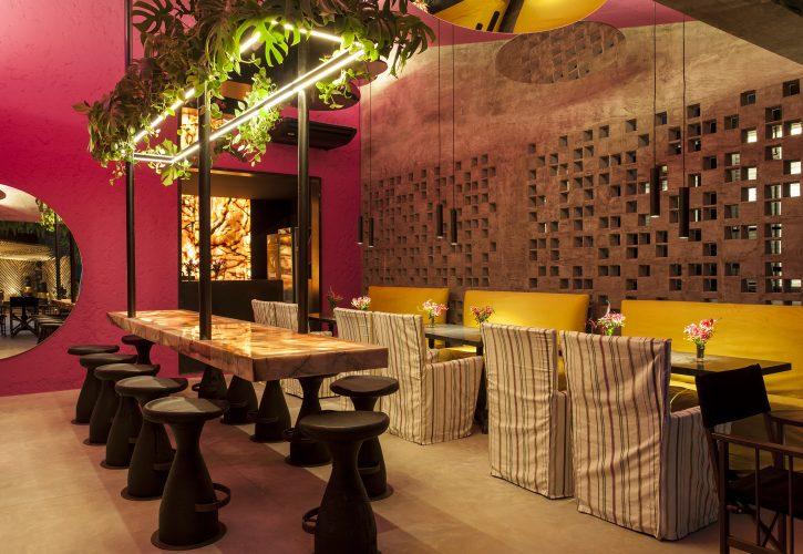 David Bastos assina restaurante Amado na CASACOR Bahia 2019, cobogós em uma parede e as restantes pintadas de rosa e espelhos redondos no teto.