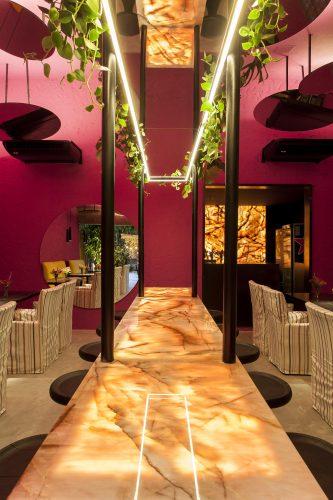 David Bastos assina restaurante Amado na CASACOR Bahia 2019, parede e teto pintado de rosa e espelhos redondos no teto.
