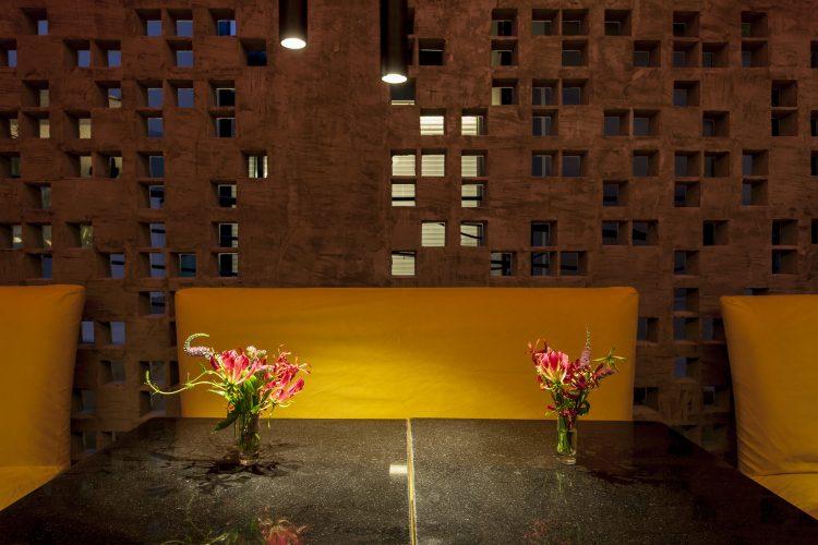 David Bastos assina restaurante Amado na CASACOR Bahia 2019, sofá amarelo e parede de cobogó atras.
