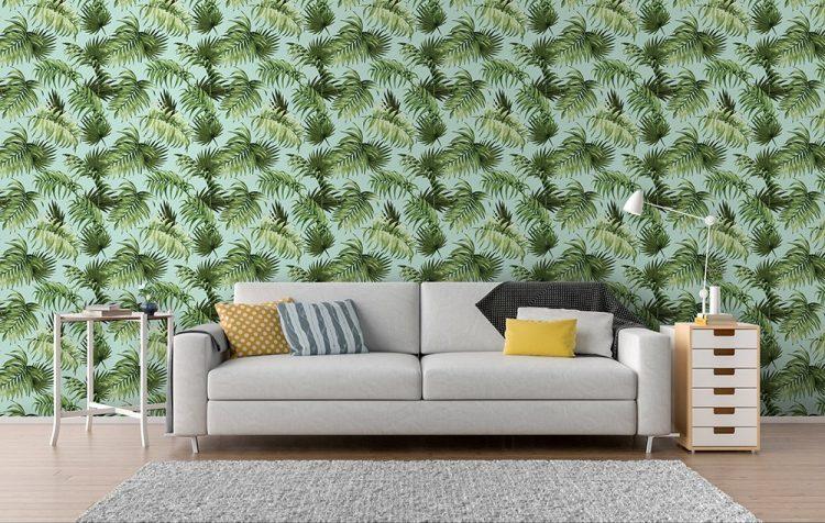 papel de parede com estampa de folhas e um sofá cinza
