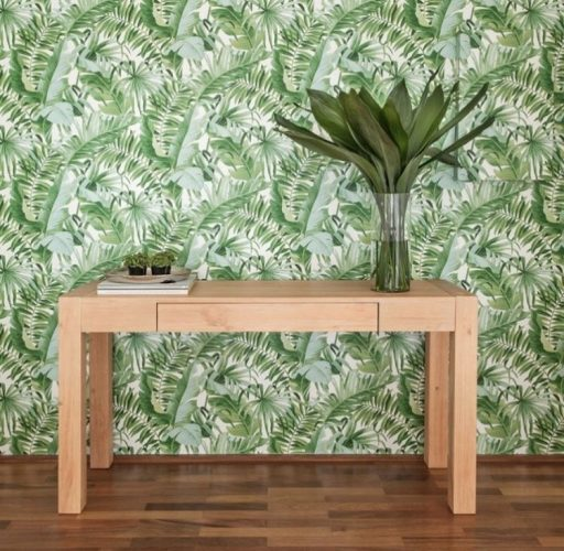 papel de parede com folhagens verde e um aparador em madeira clara em frente