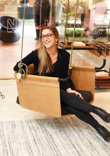 Marcella Bacellar sentada em um balanço