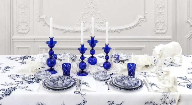 mesa posta com toalha branca bordada com flores azuis, copos e castiçais de vidro azul e louça azul e branca, da grife francesa Dior.