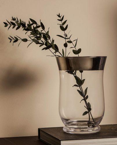 Vaso de vidro com folhagem dentro.