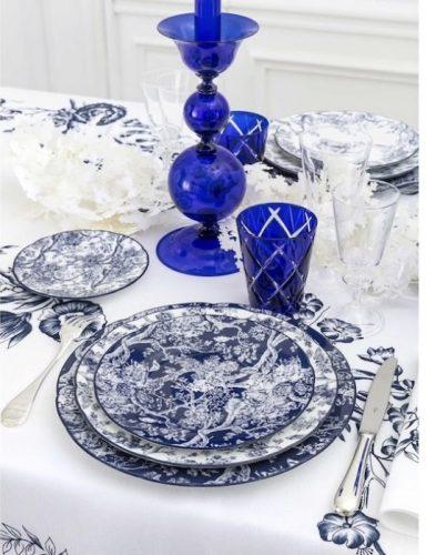 Conjunto de pratos azul a branco, copo azul e castiçal em vidro azul, da marca francesa Dior