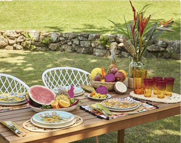 Mesa posta em um jardim com frutas e cestos enfeitando