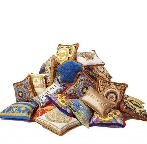 Pilha de almofadas douradas e azul da grife Versace.