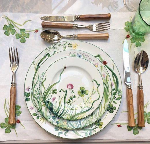 mesa posta com toalha branca com bordados, pratos brancos com estampa de flores e talheres com cabo de madeira. da grife francesa Dior