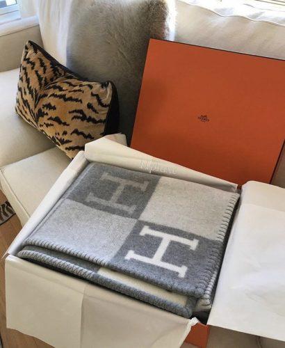 Caixa de presente da grife Hermés com uma manta de lã dentro.