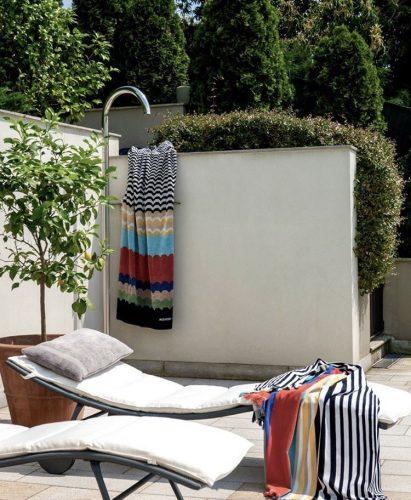 Espreguiçadeira e chuveiro em uma varanda , com toalhas listradas da grife Missoni Home.