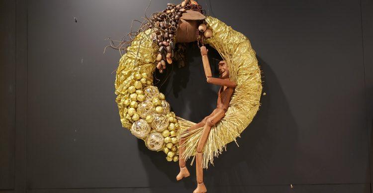 Guirlandas para o ano inteiro. Guirlanda dourada com um boneco de madeira, assinada pelo arquiteto Mario Snatos