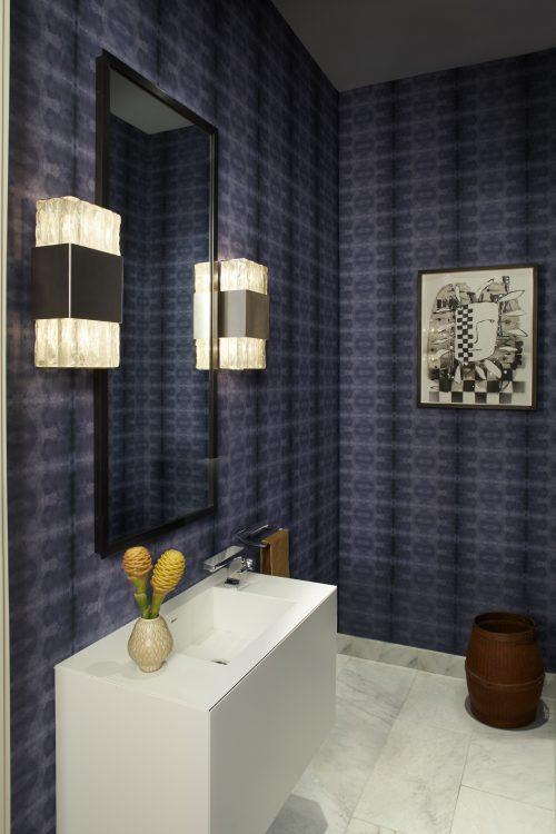 Loft em NY, lavabo com com paredes revestidas de tecido azul, luminárias art decor e bancada branca.