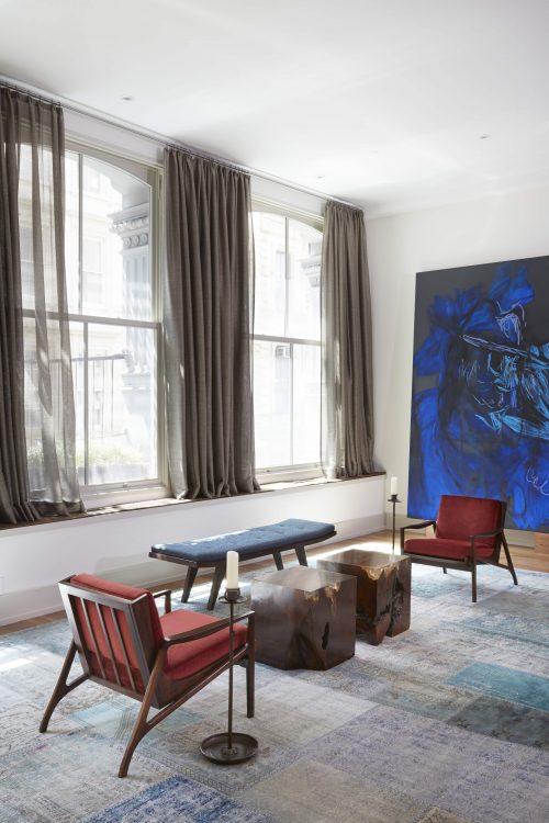 Loft em NY, poltronas vintage Joaquim Tenreiro, janelas amplas com cortina cinza e tela azul ao fundo da sala