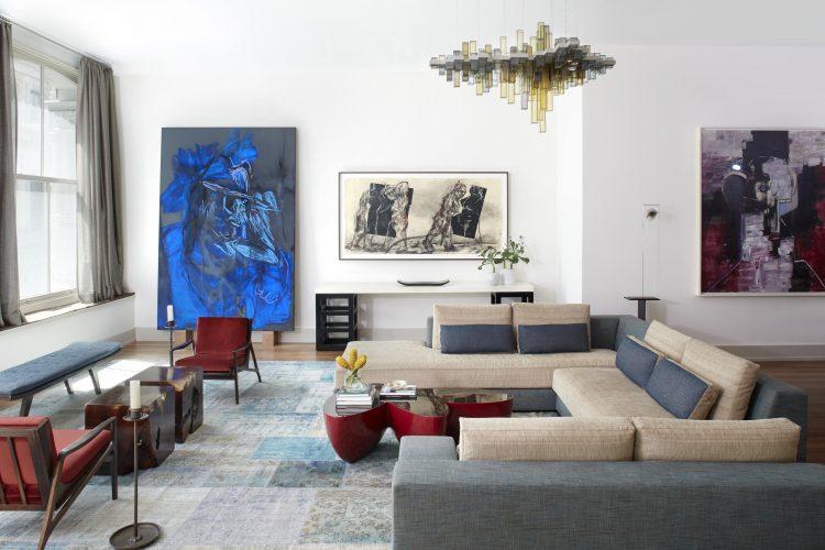 Loft em NY, sala com sofás cinza e paredes com obras de arte