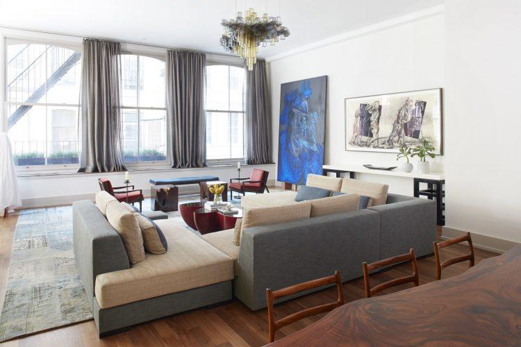 Loft em NY, sala com sofás cinza e paredes com obras de arte, janelas grandes