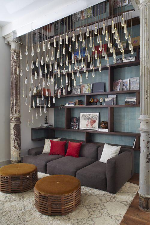 Loft em NY, cantinho com estante em madeira, sofá cinza e instalação artística de uma luminária.