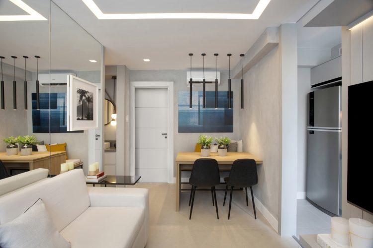Pequeno apartamento de 27m² em Piedade, Zona Norte doRio de Janeiro, prova que é possível viver com conforto e praticidade em espaços reduzidos. Sala integrada e espelho na parede