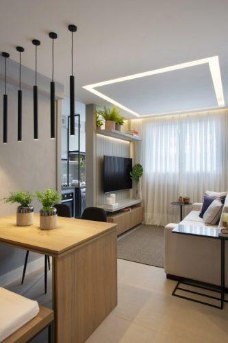 Pequeno apartamento de 27m² em Piedade, Zona Norte doRio de Janeiro, prova que é possível viver com conforto e praticidade em espaços reduzidos. Cor cinza na parede e banco na mesa de jantar em madeira.