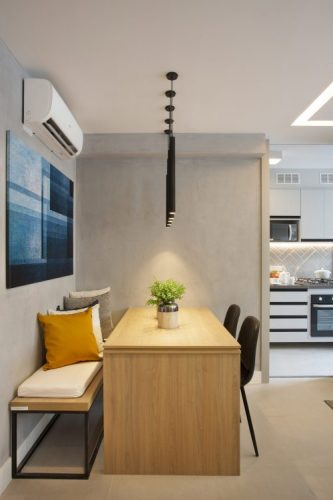 Pequeno apartamento de 27m² em Piedade, Zona Norte doRio de Janeiro, prova que é possível viver com conforto e praticidade em espaços reduzidos. Espaço integrado, banco encostado na parede, paredes em cinza e mesa de jantar em madeira.