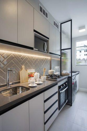 Pequeno apartamento de 27m² em Piedade, Zona Norte doRio de Janeiro, prova que é possível viver com conforto e praticidade em espaços reduzidos. Cozinha e área de serviço separada por uma divisória em esquadria preta e vidro boleado.