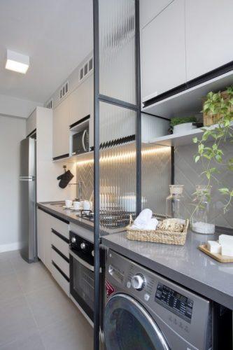 Pequeno apartamento de 27m² em Piedade, Zona Norte doRio de Janeiro, prova que é possível viver com conforto e praticidade em espaços reduzidos. Divisória em esquadria preta separa área de serviço e cozinha.
