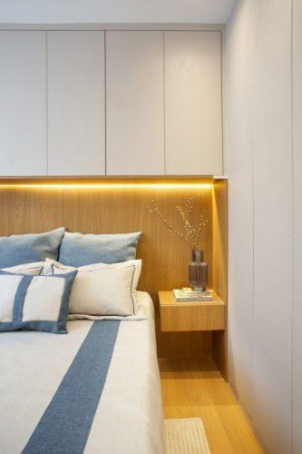 Pequeno apartamento de 27m² em Piedade, Zona Norte doRio de Janeiro, prova que é possível viver com conforto e praticidade em espaços reduzidos. Cama com nicho em madeira e armários superiores.