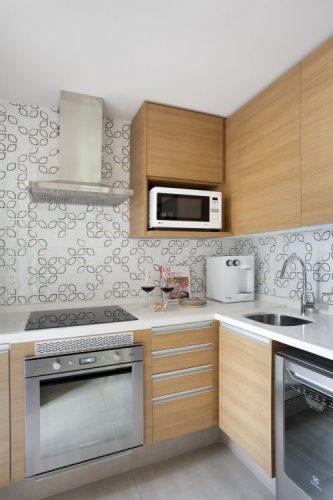Pequenas interferências para tornar os ambientes mais amplos em um apartamento no Leblon. Pequena cozinha com bancada em corian, armarios em madeira e revestimento de fundo estampada com folhas.