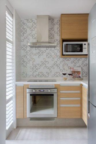 Pequenas interferências para tornar os ambientes mais amplos em um apartamento no Leblon. Pequena cozinha com cooktop, coifa e armários em madeira