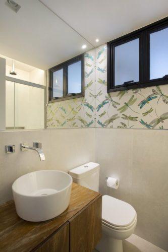 Pequenas interferências para tornar os ambientes mais amplos em um apartamento no Leblon. Lavabo m meia parede com revestimento branco e em cima papel de parede com libélulas.