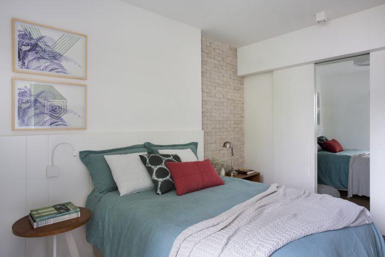 Pequenas interferências para tornar os ambientes mais amplos em um apartamento no Leblon. Parede lateral da cama em tijolinho pintado de branco