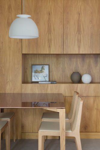 Pequenas interferências para tornar os ambientes mais amplos em um apartamento no Leblon. Parede de fundo da mesa de jantar revestida em madeira, com nicho e portas de armários camufladas