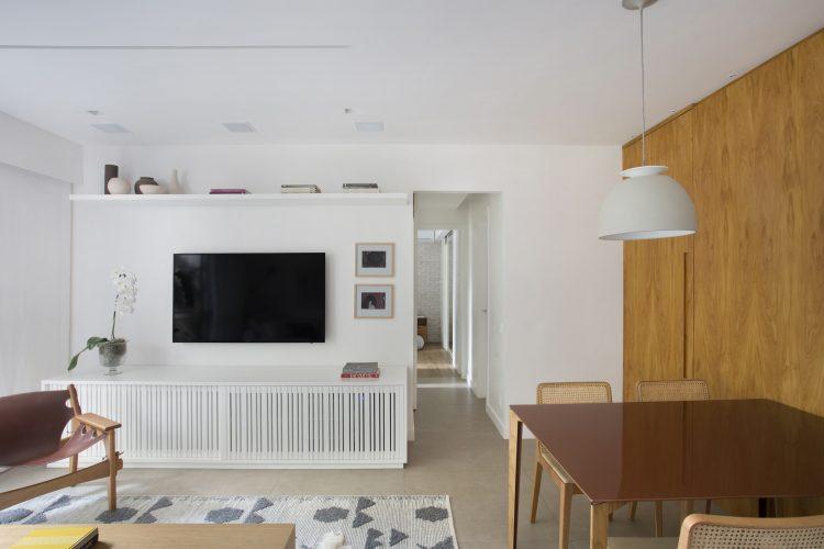 Pequenas interferências para tornar os ambientes mais amplos em um apartamento no Leblon. Parede da Tv branca, rack embaixo com ripas brancas e parede lateral da mesa de jantar revestida em madeira