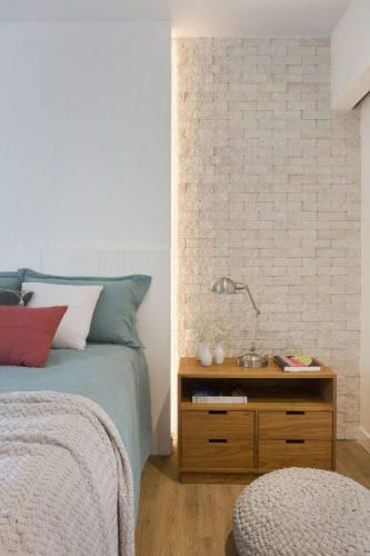 Pequenas interferências para tornar os ambientes mais amplos em um apartamento no Leblon. Painel branco atras da cama com luz embutida e lateral com tijolinho pintado de branco
