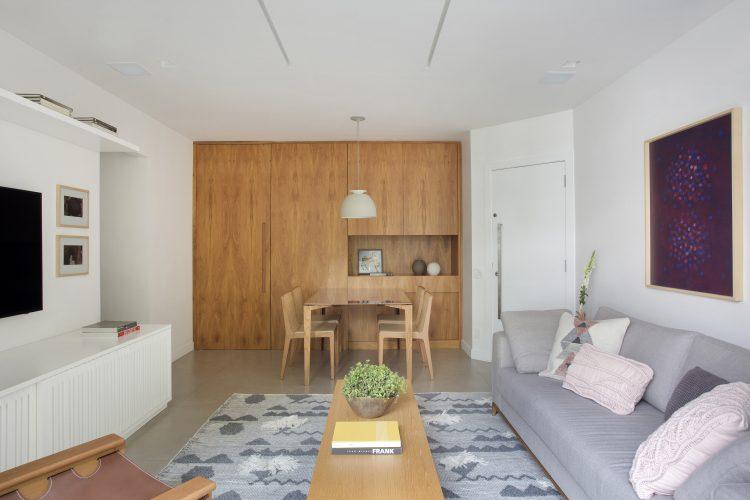 Pequenas interferências para tornar os ambientes mais amplos em um apartamento no Leblon. Funda da parede da mesa de jantar com painel em madeira