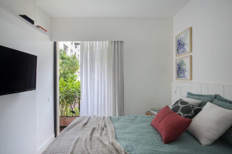 Pequenas interferências para tornar os ambientes mais amplos em um apartamento no Leblon. Quarto com sacada, painel branco com tv embutida.